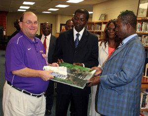 His Excellency Seraphin Moundounga, the Minister of National Education and Higher Education (center), and His Excellency René Ndémézo'o Obiang, the Minister of Culture, Youth and Sport (right), present a special commemorative book on Gabon to Daphne High School Principal Don Blanchard.