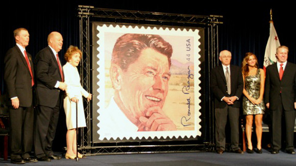 Former first Lady Nancy Reagan (left of the display) unveils a new postage stamp, designed by 1986 American Sport Artist and Archives (ASAMA) Sport Artist of the Year Bart Forbes (right of the display), to honor the late President Ronald Reagan's 100th birthday.