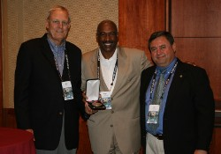 Ohio State University Associate Vice President and Director of Athletics Gene Smith (center) accepted the United States Sports Academy's 2010 Carl Maddox Sports Management Award Thursday, June 16 at the National Association of Collegiate Directors of Athletics annual convention in Orlando. Dr. Gary Cunningham (left), an Academy Board of Trustees member and 2005 winner of the Maddox award, made the presentation with Academy Vice President Dr. T.J. Rosandich (right).