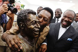 Pelé (left) plants a kiss on the bronze bust of himself
